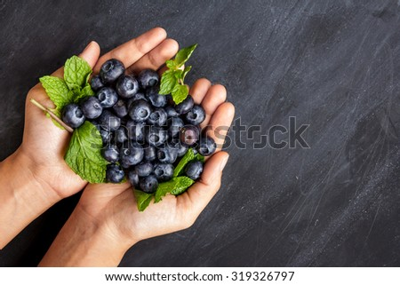 fresh blueberries in hands on black board for background with copy space - stock photo