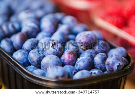 Fresh blueberry in plastic box at market, local food healthy background - stock photo