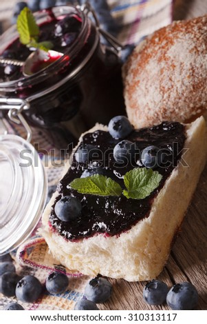 Fresh blueberry jam and sweet bun macro on the table. vertical - stock photo