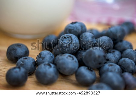 Fresh Blueberry on the wooden table and cup of Milk - stock photo