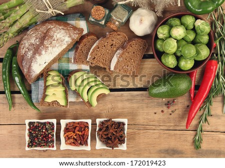 fresh bread and vegetables on wooden background - stock photo