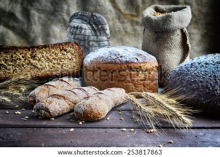 fresh bread, buns and wheat on the wooden background - stock photo