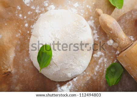 Fresh bread dough with a rolling pin on a wooden surface ready to be rolled out for a pizza base or pastry - stock photo