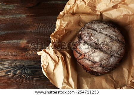Fresh bread on paper on wooden background - stock photo