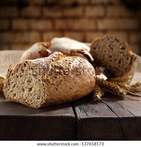 fresh bread on table in dark interior - stock photo