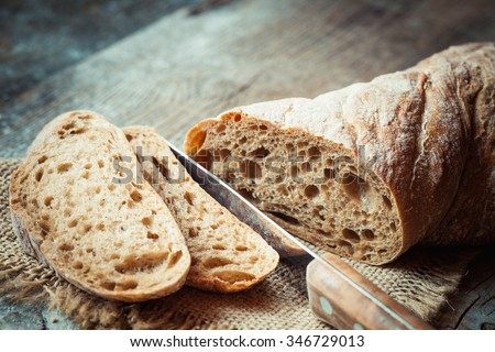 Fresh bread slice and cutting knife on rustic table - stock photo