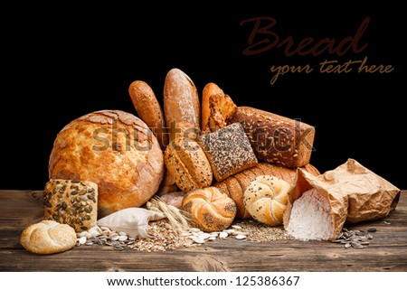 Fresh bread still life on wooden table - stock photo