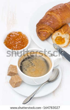 fresh breakfast with black coffee, croissants and orange jam, top view, vertical - stock photo
