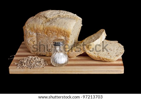 Fresh bred and some seeds on a cutting board isolated over black background - stock photo