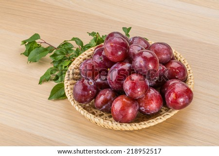 Fresh bright plums in the bowl on board - stock photo