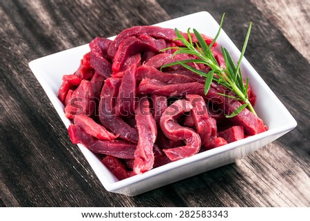 Fresh British uncocked Beef sliced meat, rosemary. - stock photo