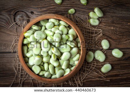Fresh broad beans in a container on a wooden table. Selective focus. Top view. - stock photo