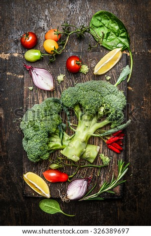 Fresh broccoli and vegetables ingredients and seasoning for tasty vegetarian cooking on rustic wooden background, top view. Diet or vegan food concept. - stock photo