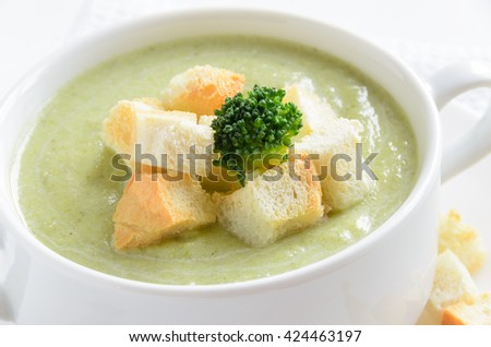 Fresh broccoli cream soup in bowl served with croutons on white background, close-up. Selective focus - stock photo