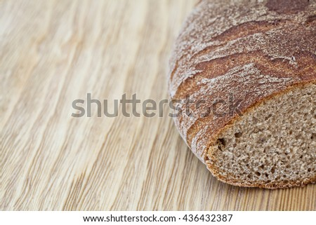 Fresh brown rye bread on a rustic wooden table - stock photo
