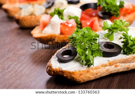Fresh bruchettas with olive on wooden table. Selective focus on the first bruschtta - stock photo