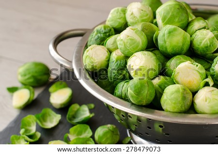 Fresh brussels sprouts in metal colander for healthy cooking selective focus - stock photo
