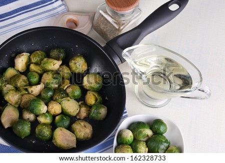 Fresh brussels sprouts in pan with vegetables and spices isolated on white - stock photo