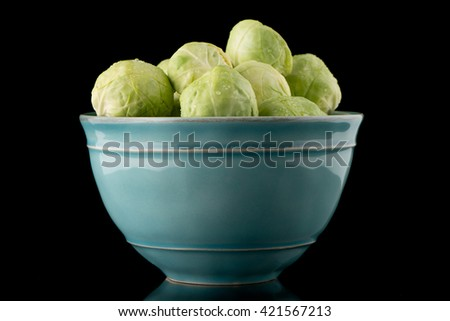 Fresh brussels sprouts on blue ceramic bowl isolated on black background. - stock photo