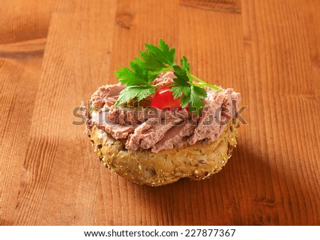 fresh bun with pate, cherry tomato and parsley on wooden table - stock photo