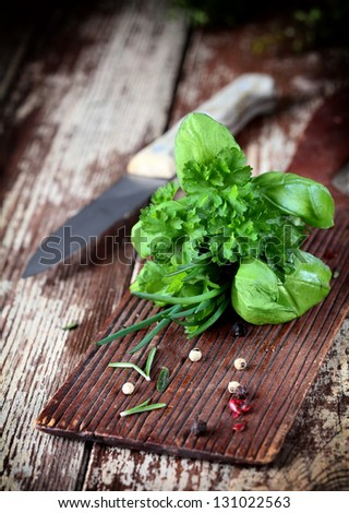 Fresh bunch of bouquet garni herbs including, rosemary, parsley, chives and basil lying on a wooden chopping board in a rustic kitchen with a knife - stock photo