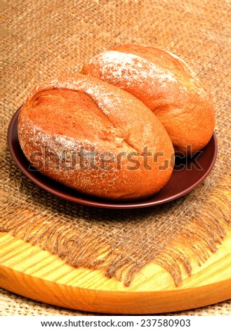 Fresh buns and rolls on the plate on the sacking background - stock photo