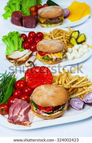 Fresh burgers in plate. Assorted delicious big hamburgers. Set of  different burgers in plate. burger ingredients - stock photo