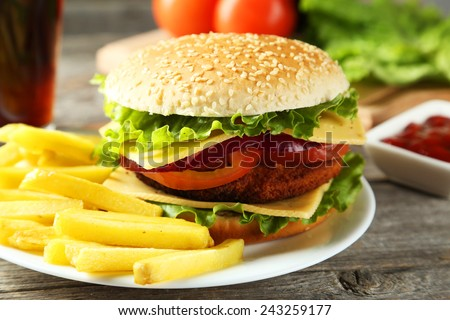 Fresh burgers on plate on grey wooden background - stock photo