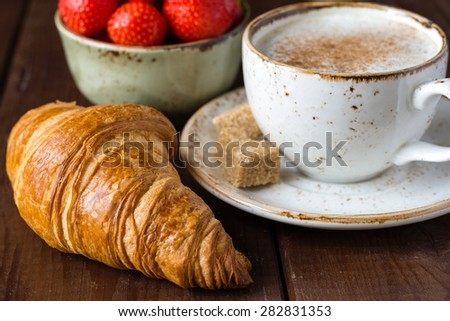 Fresh buttery croissants on brown wooden table, hot cup of coffee cappucino, cubed brown sugar and bowl with strawberries, close up - stock photo