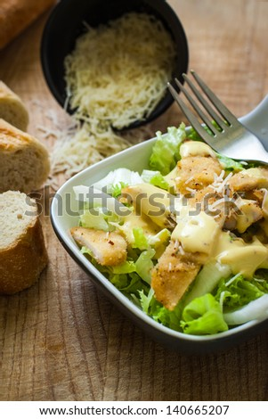fresh caesar salad on bowl with parmesan cheese - stock photo