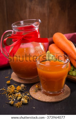 fresh carrot juice in glass and ripe raw carrot in studio - stock photo