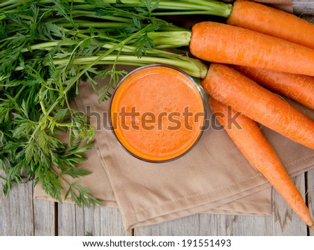 Fresh carrot juice on a wooden background - stock photo