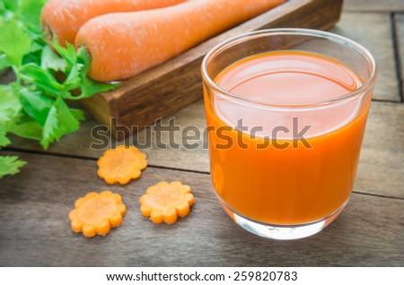 Fresh carrot juice on wooden table  - stock photo