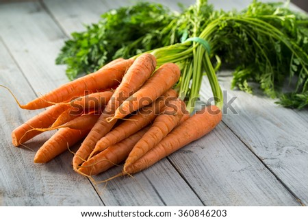 Fresh carrots bunch on wooden background - stock photo