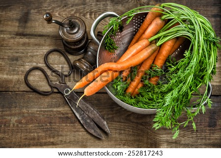 Fresh carrots with greens and vintage kitchen utensils on wooden background. Country style food concept - stock photo