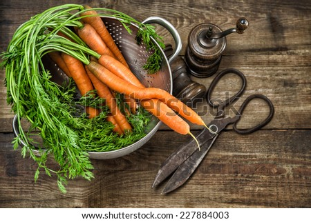 Fresh carrots with vintage kitchen utensils on rustic wooden background. Country style food concept - stock photo