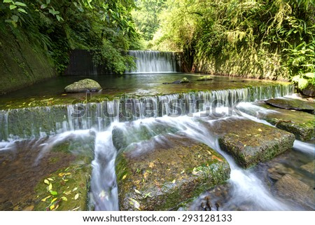 Fresh cascade in a mysterious forest with sunlight  through the lavish greenery - stock photo