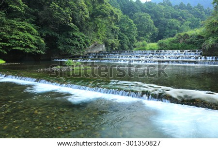 Fresh cascade in a mysterious forest with sunlight through the lavish greenery ~ Scenery of Taiwan - stock photo