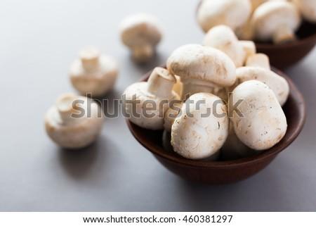Fresh champignons at black rustic table. Close up - stock photo