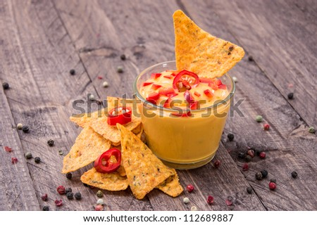 Fresh Cheese Sauce with Nachos on wooden background - stock photo