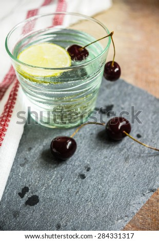 Fresh cherries and water with lime - stock photo