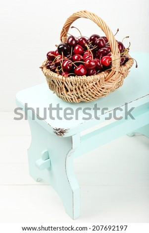 Fresh cherries in basket on white wall background - stock photo