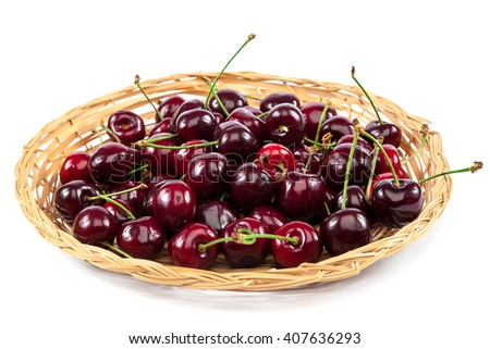 Fresh cherries on a wicker plate isolated on a white background. - stock photo
