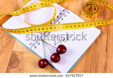 Fresh cherry and tape measure with notebook for writing notes, concept of slimming, diet and healthy nutrition - stock photo