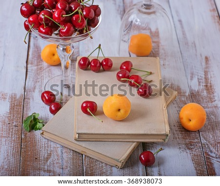 Fresh cherry, apricots and old books on a wooden table - stock photo