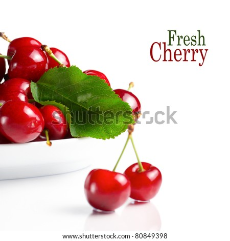 Fresh cherry berries with green leave isolated on white - stock photo