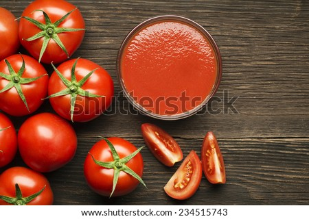 Fresh cherry tomato sauce on rustic wooden background - stock photo
