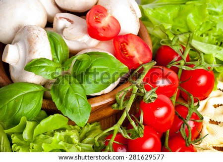 Fresh cherry tomatoes and salad in a wooden plate - stock photo