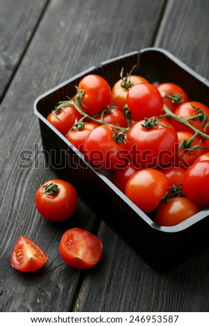 Fresh cherry tomatoes in box on black wooden background - stock photo