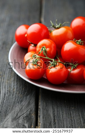 Fresh cherry tomatoes in plate on black wooden background - stock photo